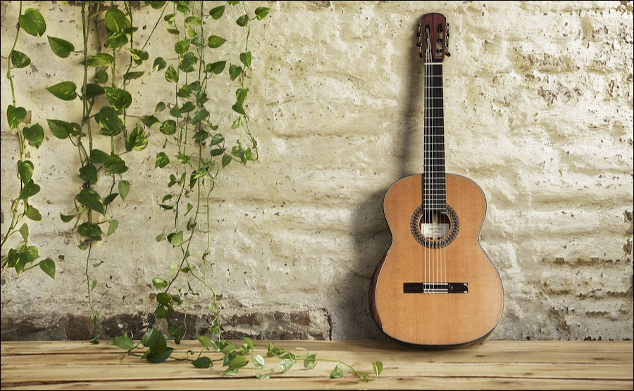 a classical guitar made by jesse moore leans against a white brick wall